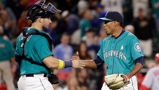 Seattle Mariners catcher Mike Zunino, left, shares congratulations with closing pitcher Edwin Diaz after the Mariners defeated the Los Angeles Angels 11-8 in a baseball game Friday, Sept. 2, 2016, in Seattle.