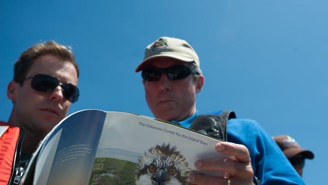 Rep. John Carney, right, looks at osprey statistics with Chris Bason.