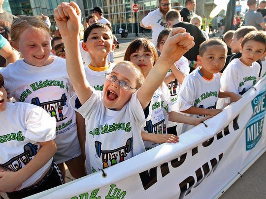 With arms raised, Morgan Cipale, center, 7, of East Des Moines, a 2nd grader at Brubaker Elementary, posed for a picture taken by his mother as he stood with other kids behind the Victory Run banner that would lead kids to the starting line for the 1/4 mile run at the Drake Relays Grand Blue Mile in downtown Des Moines on April 22, 2014.