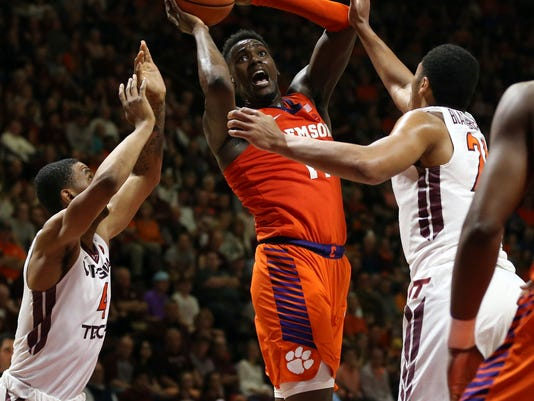 Clemson's Elijah Thomas (14) shoots while guarded by Virginia Tech's Nickeil Alexander-Walker (4) and Kerry Blackshear Jr. (24) during the first half of an NCAA college basketball game in Blacksburg Va., Wednesday, Feb. 21, 2018. (Matt Gentry/The Roanoke Times via AP)