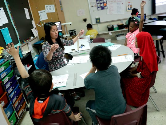Fort Howard Elementary School second-grade teacher Papaipon Rodriguez works on math skills with a small group of students June 6 in her classroom.