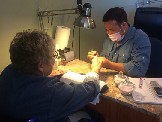 Tommy Nguyen, manager of Jasmine's Nail, helps a customer
