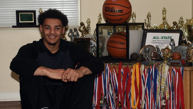 Tyler Smith sits near awards he and his brothers Alex and Robert Smith have achieved Friday, March 24, 2017 at his home in Richmond.