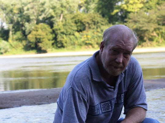 Tim Urwin, a 54-year-old Mount Auburn resident, kneels in front of the Great Miami River. He almost drowned there 15 years ago.
