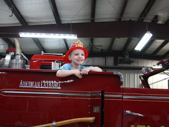 Riley Slauson is shown atop an Atlantic Fire Department fire truck in April 2014 when she was named a firefighter for the day. The fire volunteers and town at the time believed that Riley was dying from cancer. Her mother, Leatha Slauson, has since been arrested and accused of faking her daughter's illness to raise money.