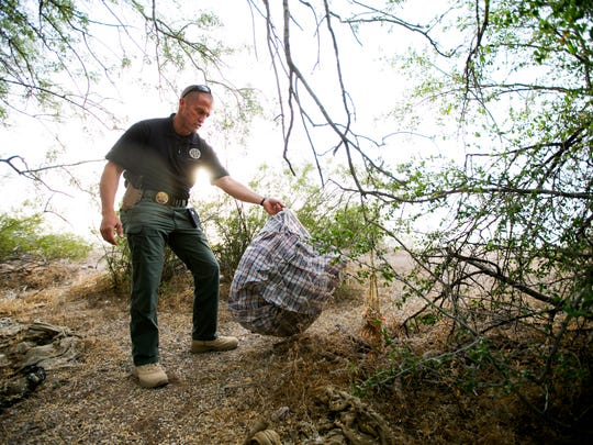 Pinal County Sheriff's Office Lt. Matthew Thomas picks up a sack that was likely used by smugglers in a drug smuggling corridor west of Casa Grande in Pinal County.