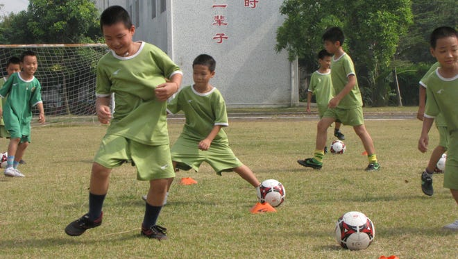 At the Qingsheng Elementary School, in a southeast suburb of south China?s Guangzhou city, kids take soccer training Saturday. ?China could become a football power, they have the talent and these kids train well,? said their coach P.K. Tresser, 26, from the Democratic Republic of Congo. ?But I see some Chinese people don?t feel football is good for their kids, so it takes a long time to change,? he said.