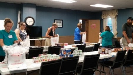 Blessings In A Backpack-Livonia volunteers sort food each Tuesday evening at a local church in preparation for its delivery to Livonia Public Schools students.