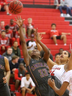 Smyrna's Kesha Brady (33) goes up for a basket after she pushes between Stewarts Creek's Ryan Odom (24) and Jasmine Smith (12) during the game Friday, Feb. 12, 2016, at Stewarts Creek.
