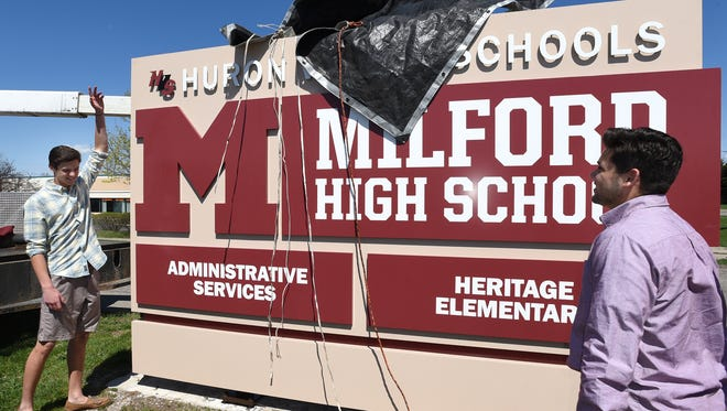 Milford High students Aiden Warzecha (left) and Joe Bravo help unveil the school's new sign near North Milford Road on April 17. The two students spearheaded the GoFundMe campaign to help replace the school's old sign.