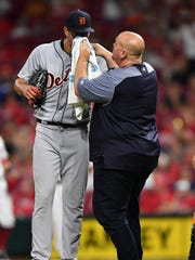 Tigers pitcher Drew VerHagen is looked after by a trainer