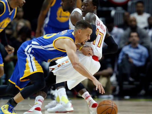 Golden State Warriors guard Stephen Curry (30) drives against Atlanta Hawks guard Dennis Schroder (17) in the first half of an NBA basketball game Monday, Feb. 22, 2016, in Atlanta. (AP Photo/John Bazemore)