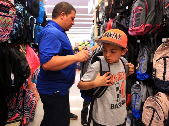 Gilbert Martinez (left) shops with his sons, including Max Martinez, 8, during a back-to-school shopping event for children selected from the Boys and Girls Clubs of the Coastal Bend at Academy Sports + Outdoors on Thursday, August 3, 2017. There were 30 children selected to spend $100 on back to school items paid for with gift cards donated by Academy.