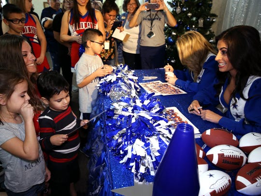 Abby Cantu (second from left) and her children Oleeva Cantu, 5 (left), and Frank Cantu, 3, get autographs from Dallas Cowboy cheerleaders  Lauren (second from right) and Jinelle at Trisun Care Center Coastal Palms in Portland on Wednesday, Dec. 20, 2017.