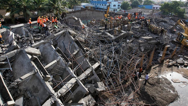 Rescue personnel search for construction workers believed buried in the rubble of a collpased 12-story apartment building outside Chennai, India.