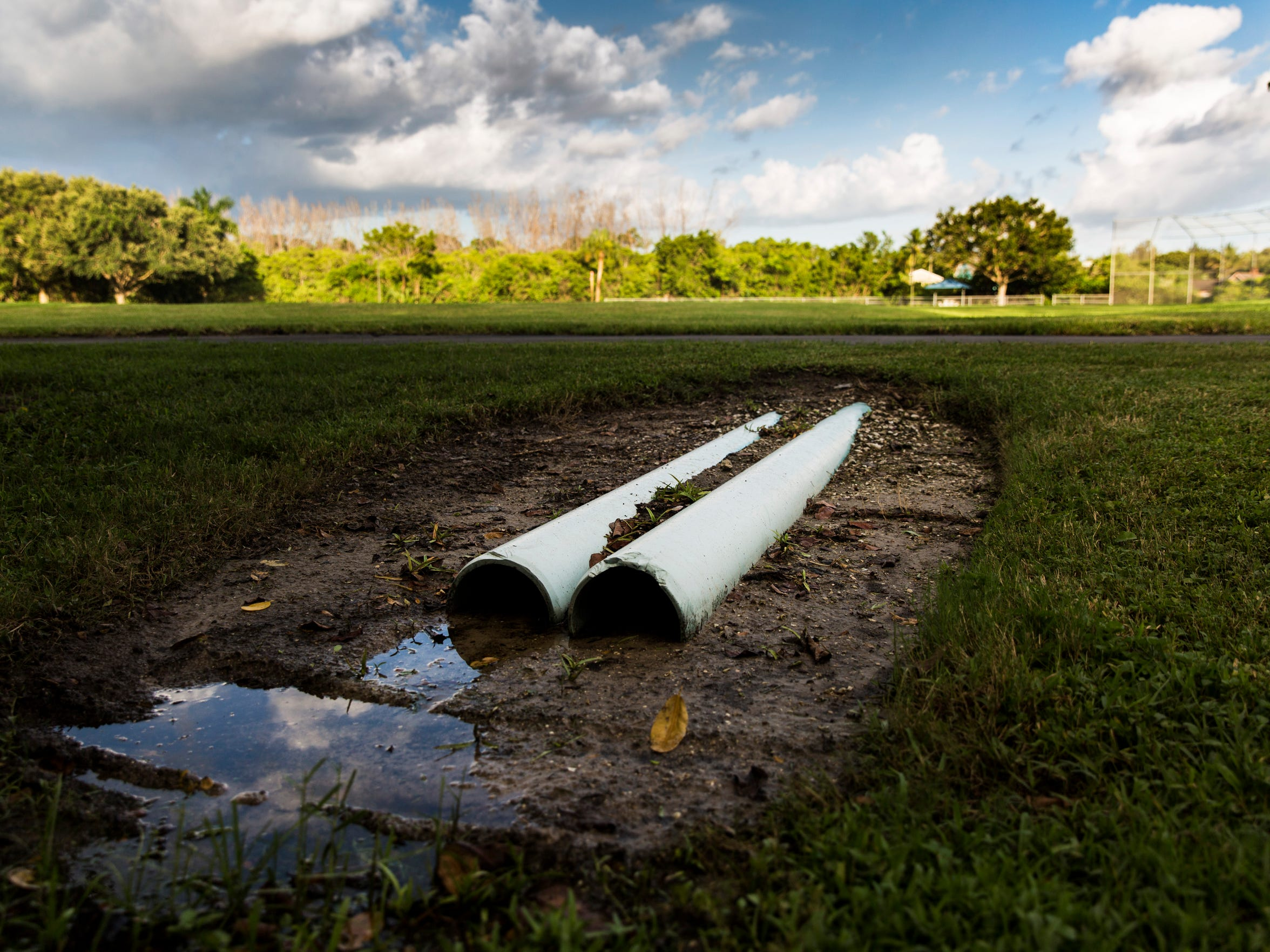 Pipes lay exposed to the side of Anthony Park on Monday, Aug. 7, 2017. The city never engineered the park's open field to drain, so it stays soggy and unusable after it rains.