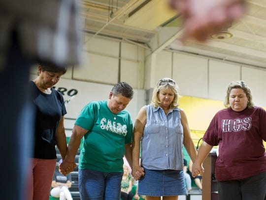 ALEX SLITZ / THE GLEANER Cairo Elementary School staff bow their heads during a prayer vigil for Cairo Elementary School principal Brian Gardner at Cairo Elementary in Henderson, Wednesday, July 13, 2016. Gardner suffered a stroke early Saturday morning.