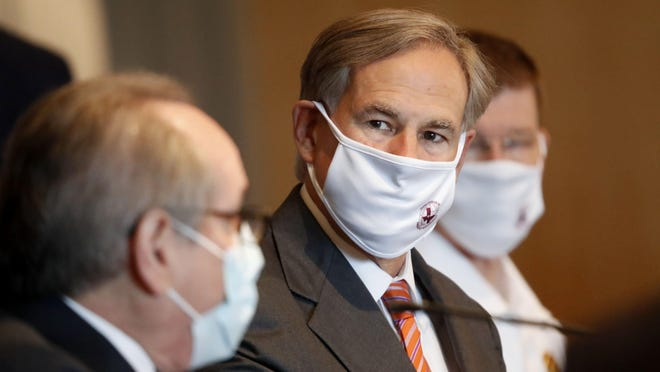 Gov. Greg Abbott, center, listens to Dr. Daniel Podolsky speak during a news conference Thursday in Dallas. University of Texas Southwestern Medical Center hosted a roundtable discussion about preparations for the upcoming flu season amid the ongoing coronavirus pandemic.
