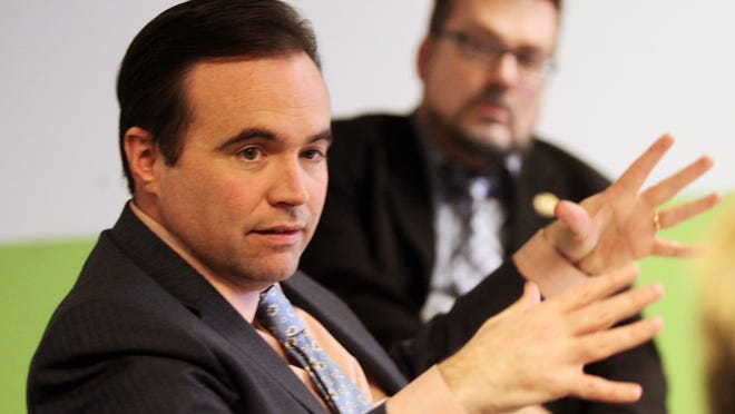 Cincinnati Mayor John Cranley answers a question during an editorial board meeting at The Enquirer. In the background is Kevin Osborne, Cranley's spokesman.