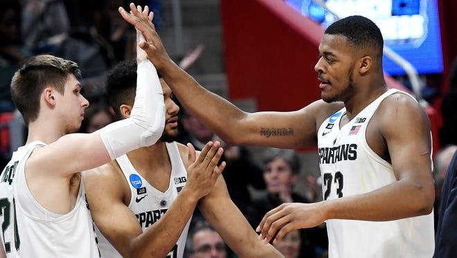 Michigan State's Xavier Tillman, right, high fives teammate Matt McQuaid after coming out of the game during the second half on Friday, March 16, 2018, at the Little Caesars Arena in Detroit. The Spartans beat Bucknell 82-78 to advance to the second round in the NCAA tournament.