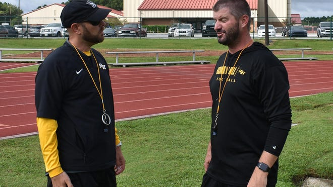 Richmond Hill head football coach Matt LeZotte, right, and assistant head coach Patrick Means in a discussion during a recent practice.