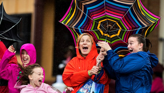 Roe Squire, left, and Annie Southworth try to wrange in their umbrella after a gust of wind came down Broadway during the KDF Pegasus Parade on Thursday. May 4, 2017