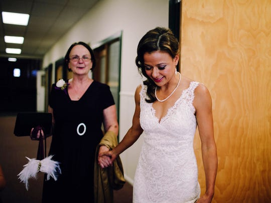 Michele Markstrom, left, the mother of the bride, Serena Markstrom, holds wings representing one of her parents before the ceremony in Eugene, Ore.