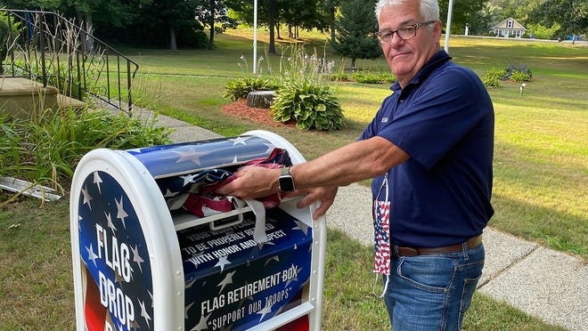 Jeffrey Nickerson, junior vice commander at American Legion Post 244 in West Brookfield, places a worn flag in a new drop box. Old flags can be dropped off anytime for the annual flag disposal ceremony.