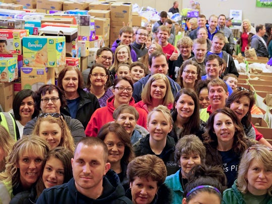 """Fox Cities crisis agency volunteers ready to sort donations to The Family Radio Network's """"Help for the Homeless"""" drive."""