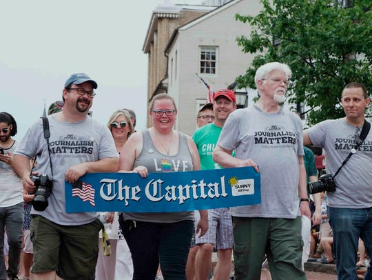 Current and former Capital Gazette staff members march