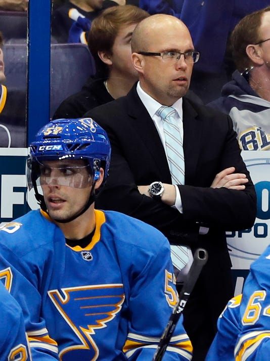 St. Louis Blues coach Mike Yeo watches from the bench alongside David Perron, left, during the second period of the team's NHL hockey game against the Toronto Maple Leafs on Thursday, Feb. 2, 2017, in St. Louis. (AP Photo/Jeff Roberson)