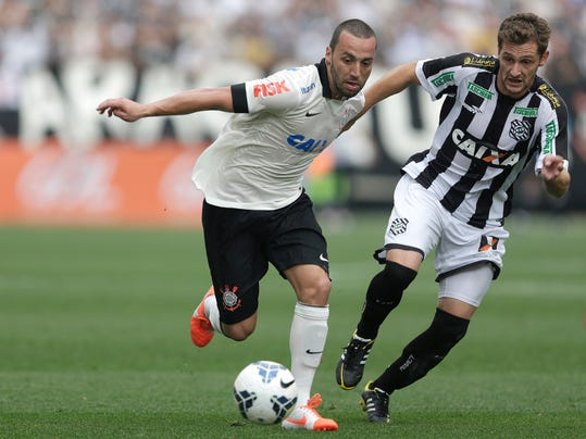 Corinthians's Guilherme, left, fights for a ball with  Figueirense's Guilherme Lazaroni during a Brazilian soccer league match at the Itaquerao, the still unfinished stadium, in Sao Paulo, Brazil, Sunday, May 18, 2014. Only 40,000 tickets were put on sale for Corinthians' match against Figueirense because some of the 20,000 temporary seats needed for the World Cup opener are still being installed. The stadium will host the World Cup opener match between Brazil and Croatia on June 12. (AP Photo/Andre Penner)