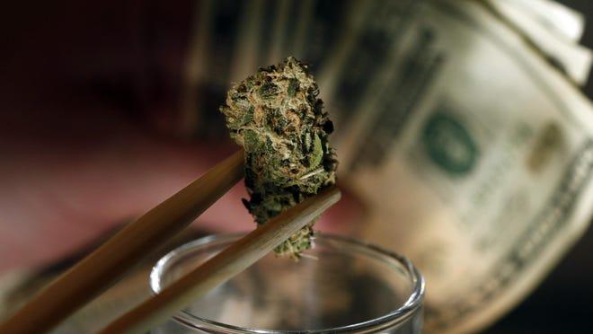 A caregiver picks out a marijuana bud for a patient at a Denver marijuana dispensary.