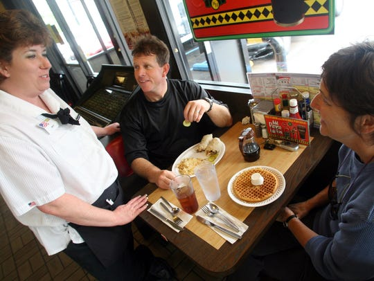 Waffle House server Marie Ellis talks with two regulars,