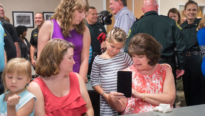 Jill Heddy shows the medal of courage to her granddaughter Brooke Heady (in striped dress) and other family members during an award ceremony at the Escambia County Sheriff's Office in Pensacola on Tuesday, August 29, 2017.  Jill's husband -correctional officer Joe Heddy, Jr. - was awarded the medal posthumously.