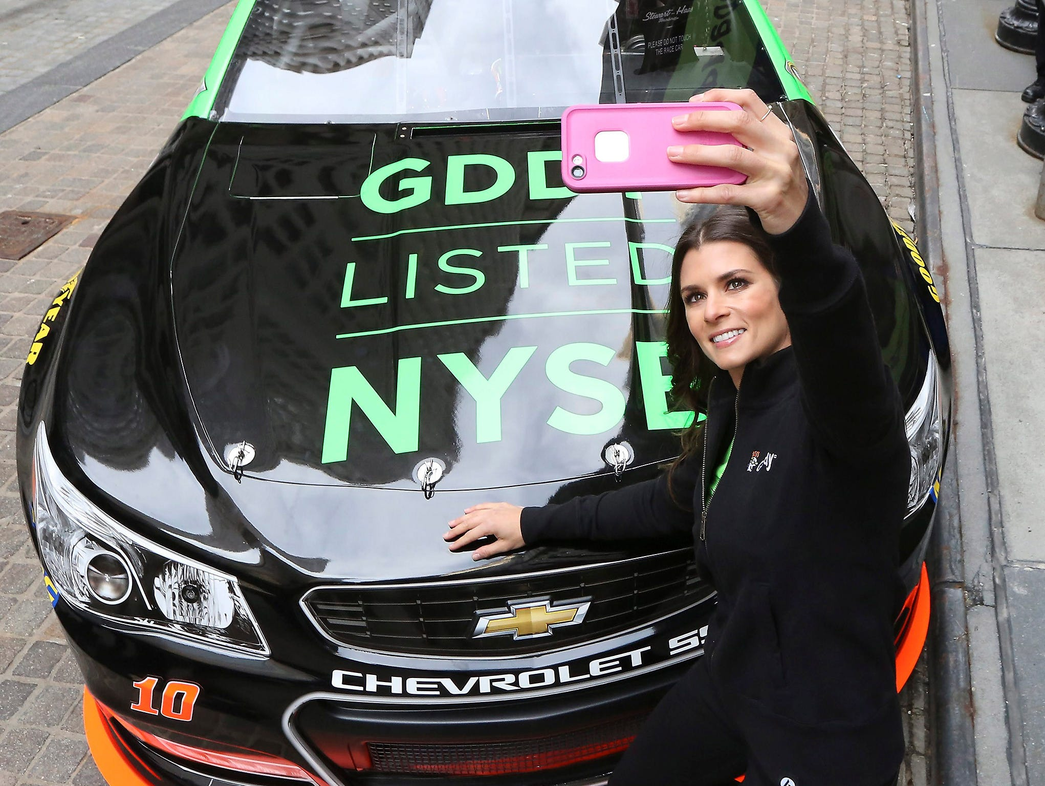epa04688909 Auto race driver and Go Daddy advertising spokeswoman Danica Patrick, shoots a self portrait of her and her race car outside the New York Stock Exchange after arriving for the Initial Public Offering of Go Daddy stocks, GDDY, in New York,
