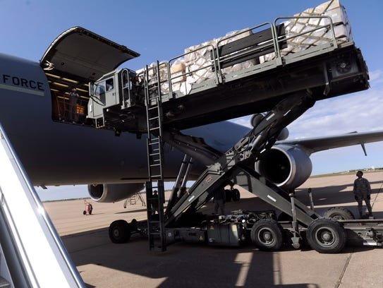 An airman watches as a 25K Loader scissors-up to load relief pallets from Global Samaritan Resources into a KC-10 U.S. Air Force cargo plane. More than 300,000 meals were loaded at Dyess Air Force Base on Friday. The food is destined for refugees in northern Iraq.