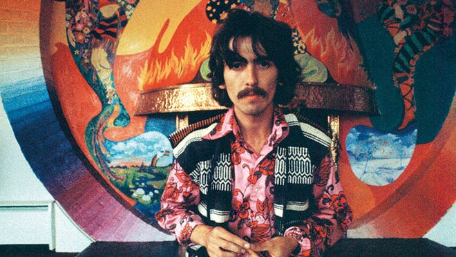 George in front of a fireplace painted by The Fool at his home Kinfauns in Esher, 1967.
