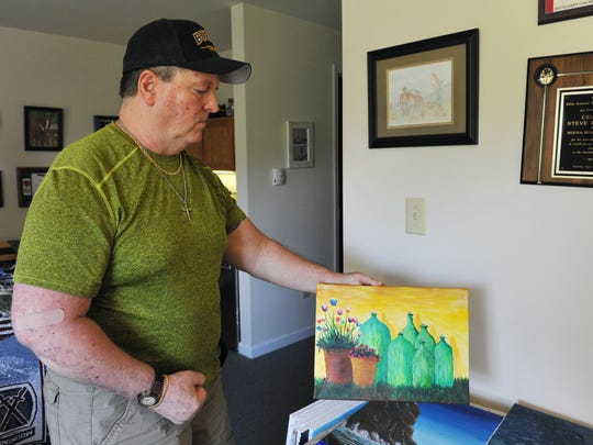 Former Buena Regional High School track coach Steve Kordos displays one of his paintings.