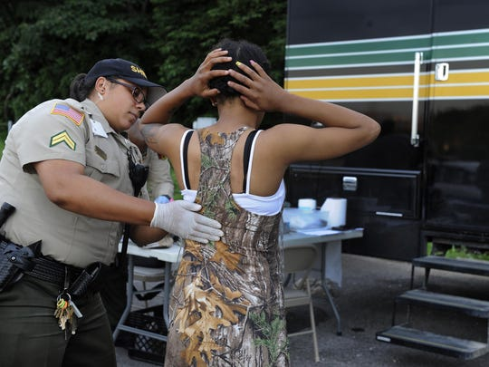 Cpl. Christina Tetterton at the Davidson County Sheriff's Office's mobile booking unit pats down a woman who was arrested for shoplifting.