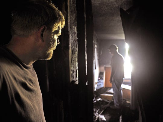 Contractors Andrew Jackson and his father Dave, right, look over the damage to the abandoned Harding Inn at 348 Harding Place after a fire ripped through the fourth floor of the inn Tuesday night, trapping homeless people on the balconies.