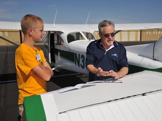 Greg Stanley, a Pathways to Aviation board member, signs a student's flight log after his first flight at a Young Eagles event.