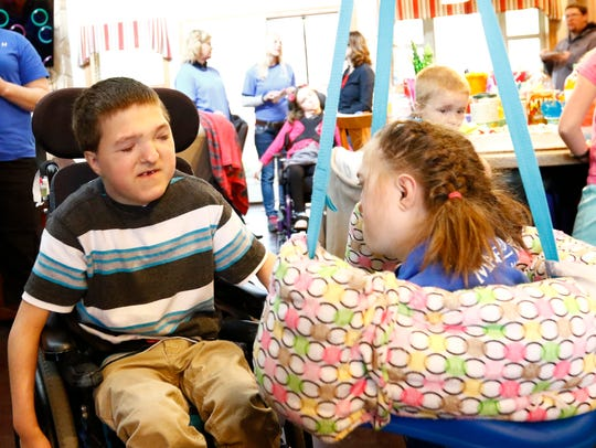 Zachary Teeters, 11, left, interacts with his sister