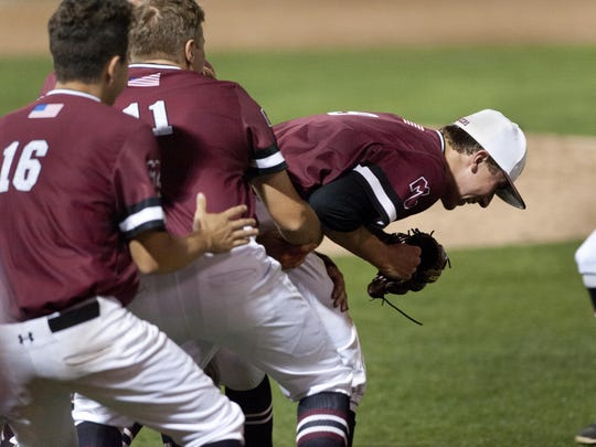 Mt. Whitney teammates swarm pitcher Holden Powell after their 1-0 win against Redwood in a West Yosemite League game at Recreation Park on Monday, May 9, 2016.