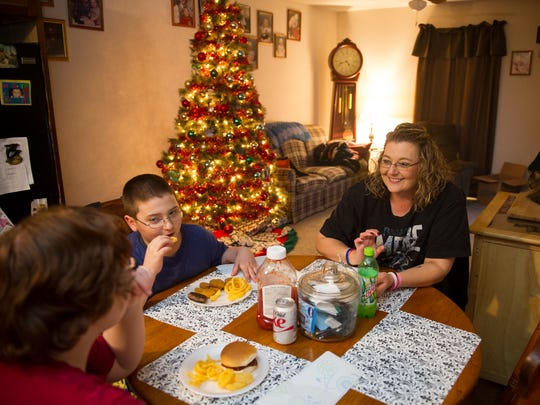 """Hannah Turner, 16, from left, eats dinner with her brother, Brason Darden, 8, and her mother, Crystal Causey, in their new home in Henderson, Thursday, Dec. 15, 2016. In their apartment they lacked space to eat meals around a table and Causey wanted a space in the new home where they could eat together daily, """"I think we've gotten closer, we can tolerate each other better,"""" Causey joked."""