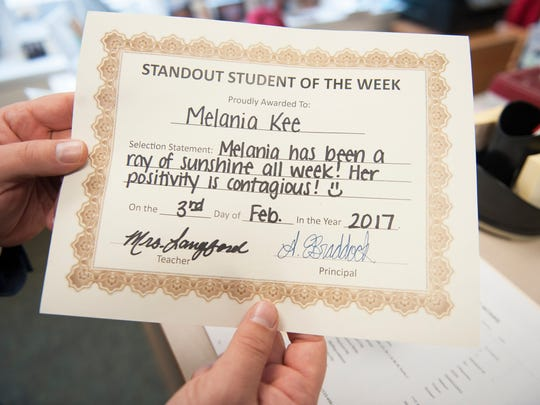 Tom Braddock, principal of Evergreen Avenue Elementary School in Woodbury, displays a certificate for fifth grader Melania Kee prior to Braddock visiting Kee's home on Friday afternoon to present her with the certificate and a special pencil to honor her for being a standout student of the week.