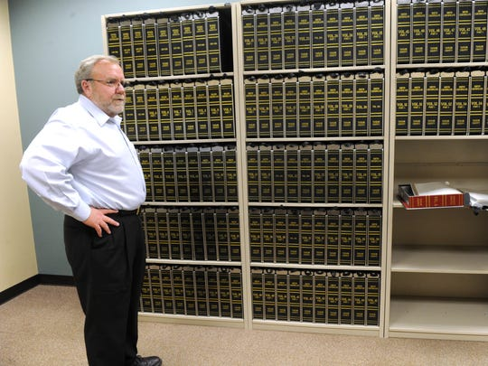 Taylor County Clerk Larry Bevill stands next to archival boxes of death and birth records at the Taylor County Courthouse.