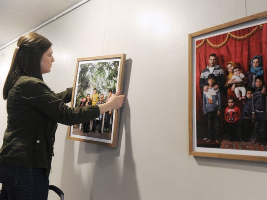 Jessica Watson, director of connections at Aldersgate United Methodist Church hangs photos of Syrian refugees, taken in Lebanon and Jordan.