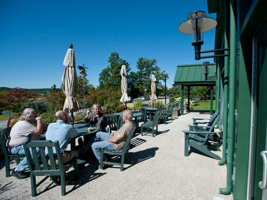Employees enjoy the sunshine during a break outside Renewable NRG Systems common area and patio in Hinesburg in 2013.