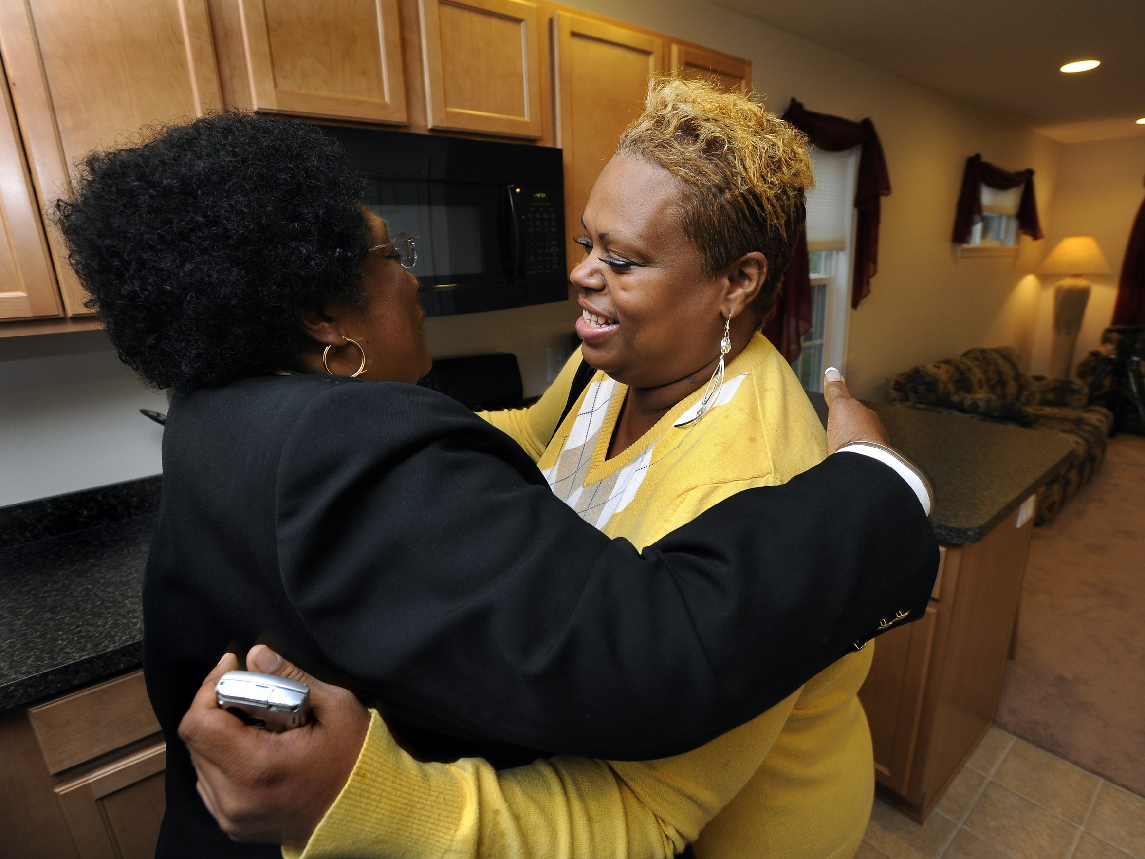 Homeowner Tonya Ellis, right, hugs Joan Jackson Johnson, City of Lansing Director of Human Relation and Community Services, during a tour of the home Ellis will live in with her nine children in Lansing Wednesday  October 13, 2010.
